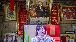 Unter einem Foto von Staats- und Parteichef Xi ist auf einem TV-Gerät ein Mann in einer Talkshow zu sehen.