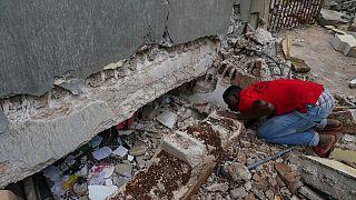 Um homem olha pelo buraco aberto numa escola afetada pelo sismo