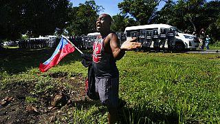 Un migrante haitiano suplica a las fuerzas mexicanas que no le detengan mientras sostiene una bandera de su país