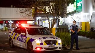 Police stand outside the site of a knife attack at a supermarket in Auckland.