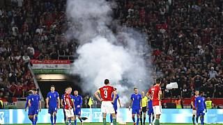 Players wait after a flare was thrown on the field during the World Cup 2022 qualifying match between Hungary and England, in Budapest, Hungary, Sept. 2, 2021.