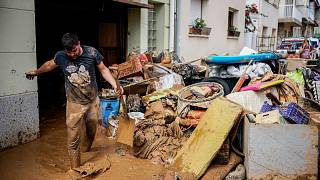 A man cleans up mud after flooding in a seaside town of Alcanar
