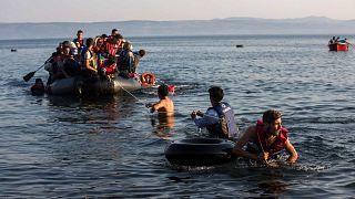 مهاجرون يسحبون زورقًا مكتظًا باللاجئين السوريين والأفغان الذين يصلون من السواحل التركية إلى جزيرة ليسبوس اليونانية، الإثنين، 27 يوليو/تموز 2015
