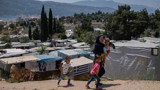 An Afghan woman with her three children walk outside the perimeter of the refugee camp at the port of Vathy on the eastern Aegean island of Samos, Greece, June 11, 2021.