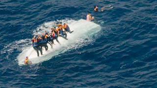 Migrants clinging to an overturned boat