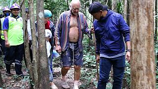 Rescuers lead Barry Leonard Weller, 72, out of the jungle, in Thailand's northeastern Khon Kaen province, Friday, Sept. 3, 2021.