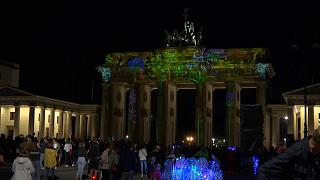 Brandenburg Gate with crowds of people at opening of Festival of Lights event.