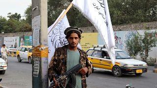Un combatiente talibán sostiene su arma bajo las banderas talibanes colgadas en una calle de Kabul, Afganistán, el 30 de agosto de 2021.