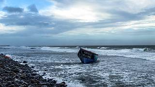 FILE: A wooden boat used by migrants from Morocco is seen grounded on the beach at the southeastern coast of the island of Gran Canaria, Spain, on Thursday, Jan. 7, 2021.