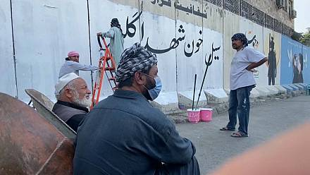 Taliban cover murals on the security wall around Kabul