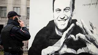 A police officer speaks on the phone near to graffiti of Russia's imprisoned opposition leader Alexei Navalny in St. Petersburg.