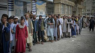 Afghans queue up as they wait for the banks to open and operate at a commercial area in Kabul on August 31, 2021.