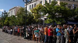 People wait outside the Athens Cathedral to pay respects to the late Greek composer Mikis Theodorakis in Athens on Monday Sept. 6, 2021.