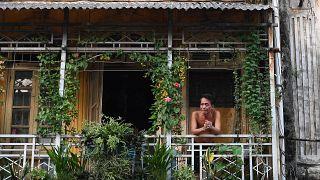 رجل ينظر من شرفة منزله في هانوي، أثناء الإغلاق  الصارم الذي فرضته الحكومة