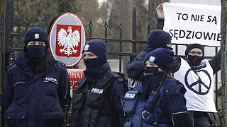 Police surround a protester who holds a sign saying in front of the Constitutional Court in Warsaw, Poland, Wednesday March 10, 2021
