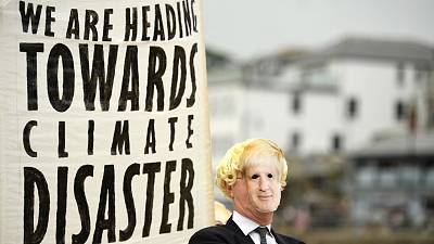 Environmental activist wears a face masks of Britain's Prime Minister Boris Johnson at the G7 summit earlier this year.