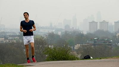 A man jogs up Primrose Hill as buildings in central London stand shrouded in smog.