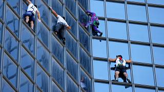 """French urban climber Alain Robert (2R), popularly known as the """"French Spiderman"""" climbs  the Total tower in La Defense near Paris, on September 7, 2021."""