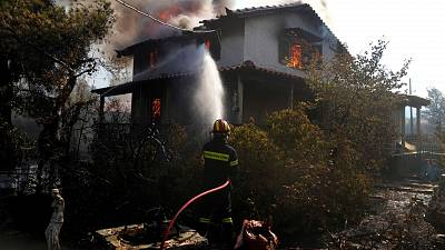 A firefighter tries to extinguish the flames at a burning house 60 kilometers northwest of Athens, Greece