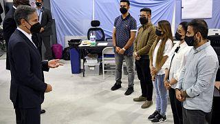 وزير الخارجية الأمريكي أنتوني بلينكين ووزير الدفاع لويد أوستن يلتقيان مع مترجمين أفغان في قاعدة العديد الجوية، التي تأوي لاجئين أفغان، في الدوحة ، قطر.