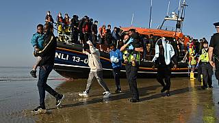 Migrants with children are escorted to be processed after being picked up by an RNLI lifeboat.