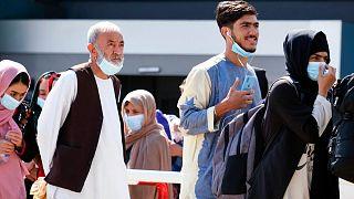 People evacuated from Afghanistan arrive at the Rome Leonardo da Vinci airport, Saturday, Aug. 28, 2021.