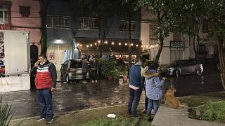 People gather outside on the sidewalk after a strong earthquake was felt, in the Roma neighbourhood of Mexico City, Tuesday, Sept. 7, 2021.