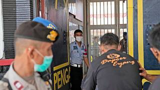 Staff and police officers guard the main entrance gate of Tangerang prison in Tangerang on the outskirts of Jakarta, Indonesia, Wednesday, Sept. 8, 2021.