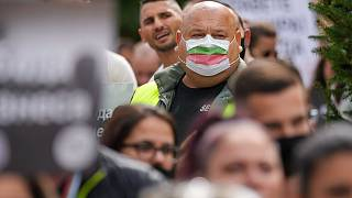 A man wears a mask in the colors of the Bulgarian flag while attending a protest by restaurant workers in Veliko Tarnovo, Bulgaria, Thursday, Sept. 2
