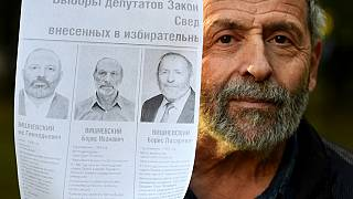 Boris (Lazarevich) Vishnevsky holds a photocopy of a poster with candidates running for election to the regional parliament in Saint Petersburg.
