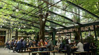 Májusi felvétel: vendégek ülnek a Schweizerhaus sörkertben a bécsi Práterben