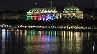 منظر لفندق فورسيزونز مضاء بألوان قوس قزح في مدينة هامبورغ، ألمانيا.