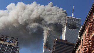 دخان يتصاعد من برجي مركز التجارة العالمي المحتر��ين بعد اعتداءات 9 سبتمبر/أيلول في مدينة نيويورك