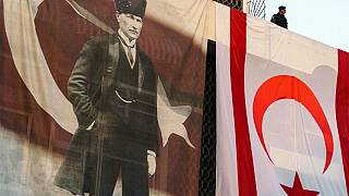 A member of the security forces stands above a large Turkish Cypriot flag and poster of modern Turkey's founder Mustafa Kemal Ataturk.
