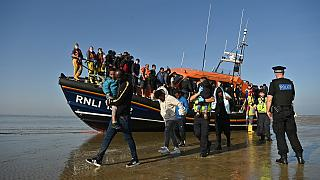 Migrants are escorted after being picked up by an RNLI (Royal National Lifeboat Institution) lifeboat while crossing the English channel, Dungeness, September 7, 2021.England