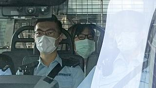 Chow Han Tung, vice chairwoman of the Hong Kong Alliance in Support of Patriotic Democratic Movements of China, center, is escorted by police in a van to a court, in Hong Kong