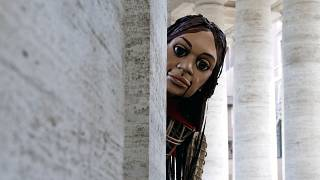 A giant puppet - called Little Amal - depicting a young Syrian refugee girl arrives at St. Peter's square in the Vatican.