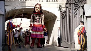 El papa saluda a la pequeña Amal, la marioneta gigante que representa a una niña refugiada siria