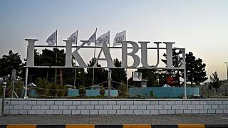 The Taliban flags are pictured behind a sign installed outside the airport in Kabul on September 9, 2021.