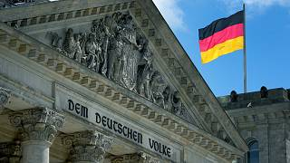 A German national flag waves on top of the German federal parliament, Bundestag, at the Reichstag building in Berlin, Germany, Wednesday, May 19, 2021.