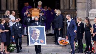Pallbearers carry a portrait and the coffin of Jean-Paul Belmondo after the funeral ceremony for the late French actor.