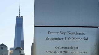 The One World Trade Center is seen behind a memorial plaque at the Empty Sky 9/11 Memorial in Liberty State Park in Jersey City.