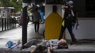 صورة لامرأة لبنانية تنظر إلى مواطن ينامُ على الرصيف في شارع الحمراء وسط بيروت 17 تموز/يوليو 2020