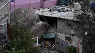 A boulder that plunged from a mountainside rests among homes in Tlalnepantla, on the outskirts of Mexico City.