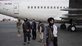 Tálibok állnak egy repülőgép mellett szeptember 9-én csütörtökön a kabuli repülőtéren, amikor több száz amerikainak sikerült elhagynia Afganisztánt