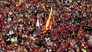 """People wave Catalan pro-independence """"Estelada"""" flags during a demonstration marking the """"Diada"""", national day of Catalonia, in Barcelona on September 11, 2021."""