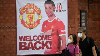 Fans walk past a banner featuring Manchester United's new signing Cristiano Ronaldo at Old Trafford stadium.