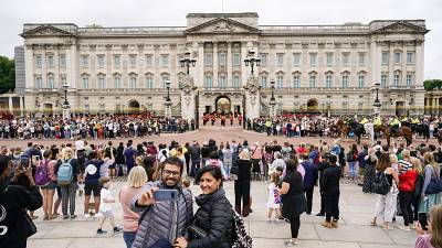 Members of the public watch the Changing of the Guard ceremony at Buckingham Palace, London, Monday August 23, 2021
