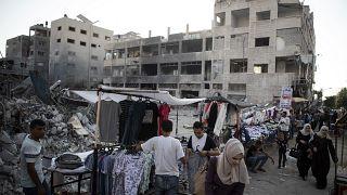 باعة فلسطينيون متجولون يعرضون سلعهم بالقرب من المباني التي دمرتها الغارات الإسرائيلية. 2021/07/18