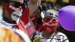 """معارضة برازيلية تلبس قناعاً كتب عليه """"بولسونارو خارجاً"""""""